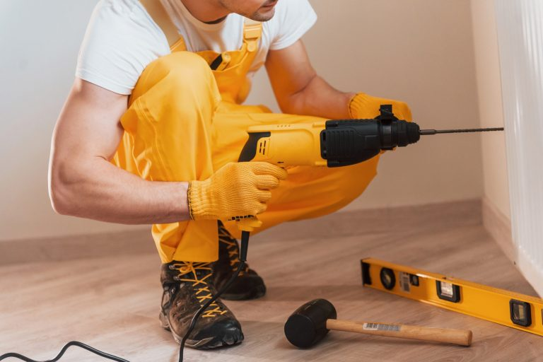 Handyman in yellow uniform works indoors by using hammer drill. House renovation conception