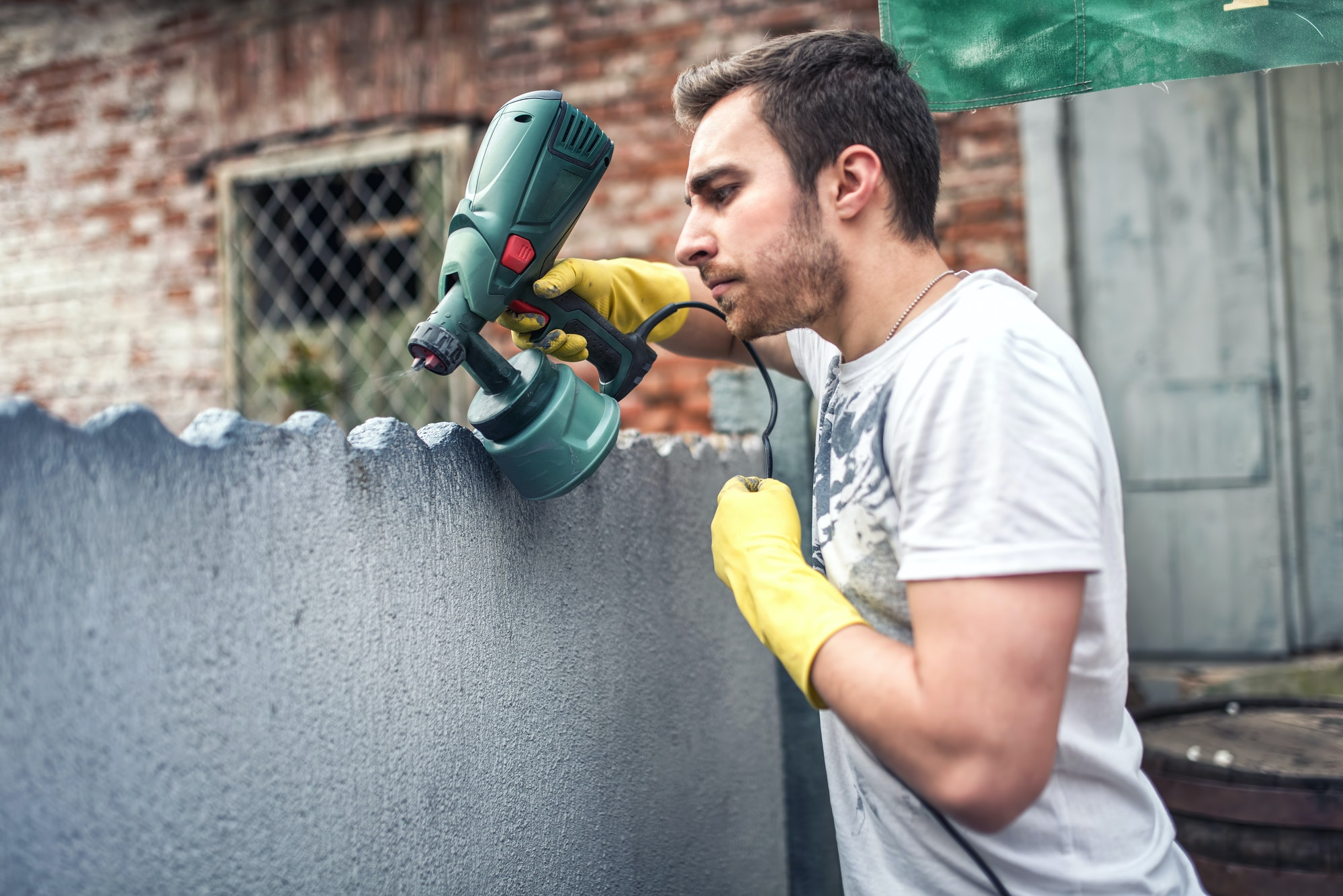 Professional construction worker painting walls at house renovation